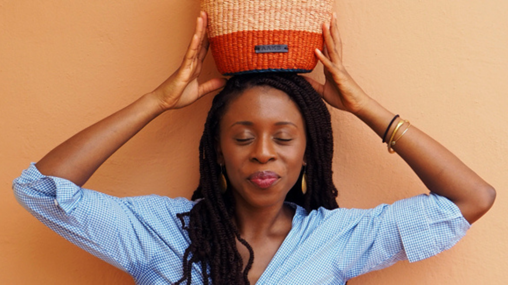 AKOSUA THE FOUNDER OF AAKS WEARING A BLUE SHIRT HOLDING HER ORANGE BAG