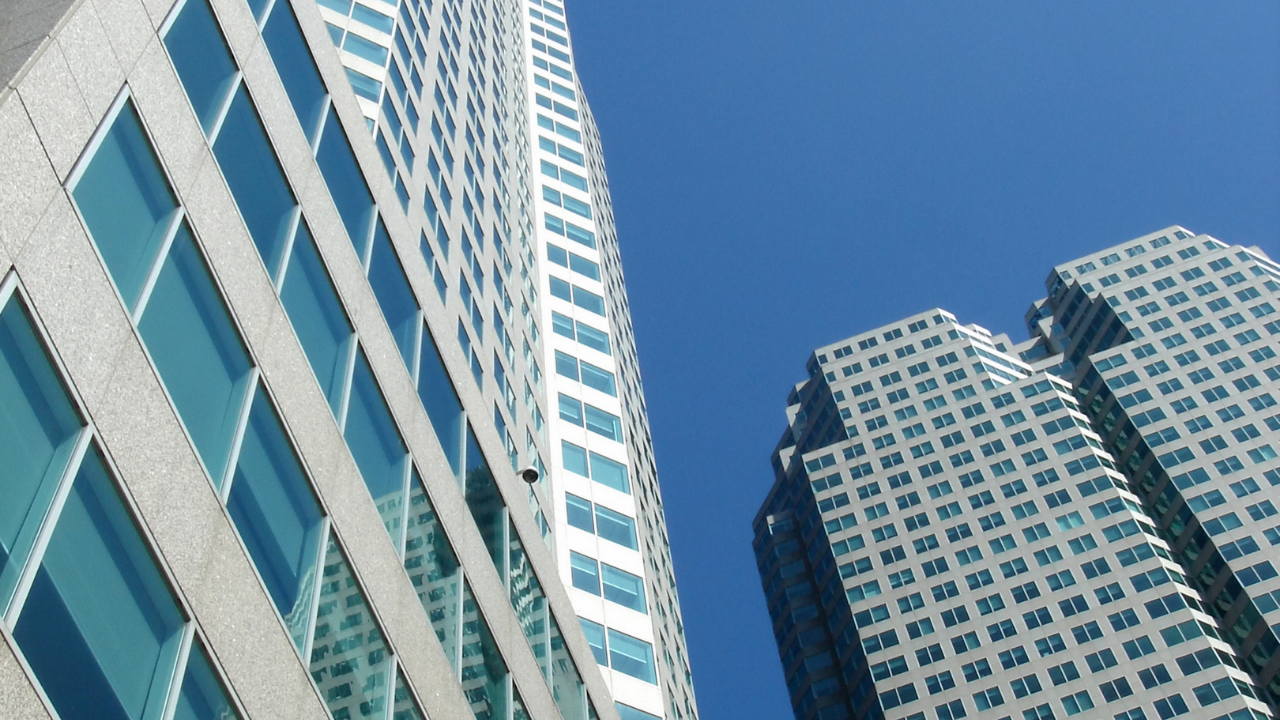 two large high rise buildings on a bright day with blue sky