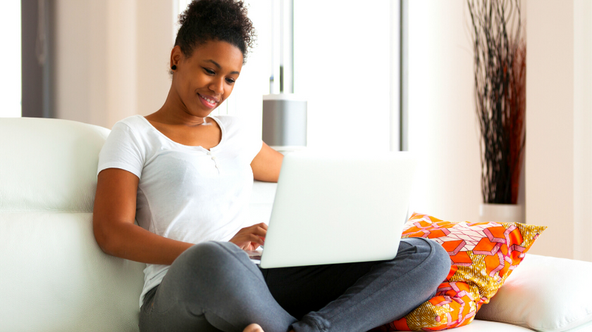 a woman in a white tshirt and jeans sitting on a couch holding a laptop