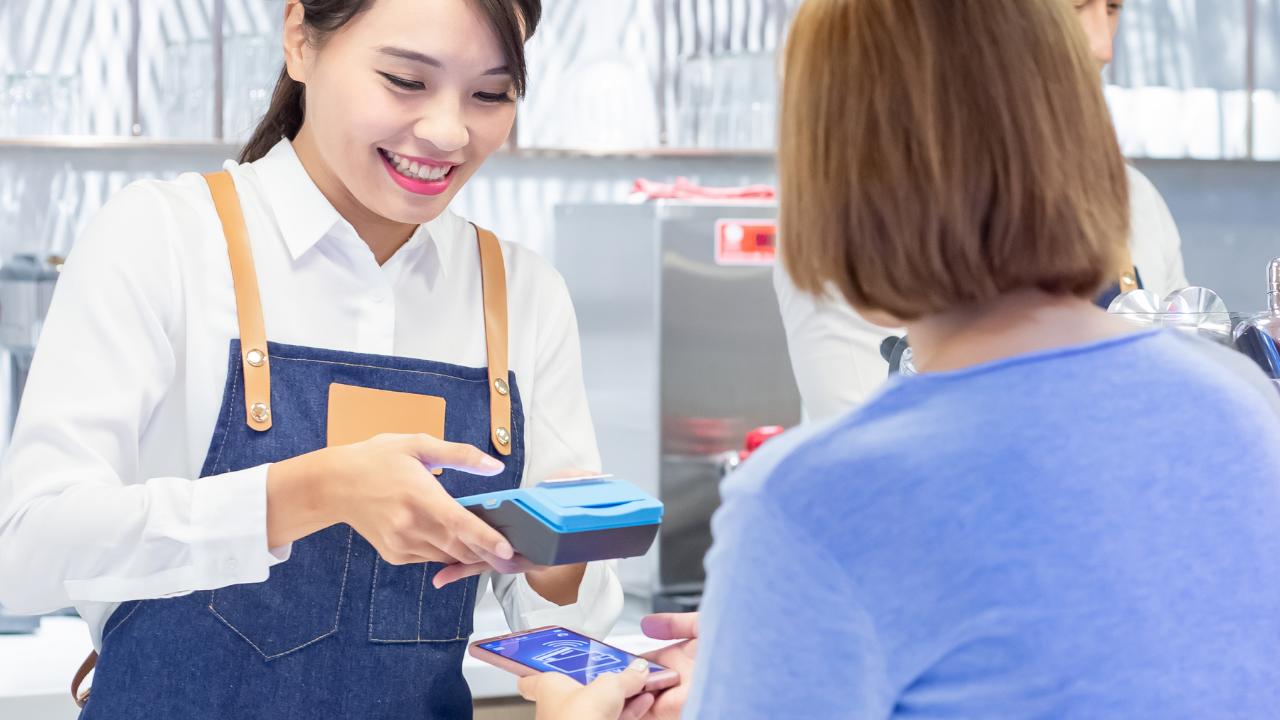 an asian woman taking a payment via machine