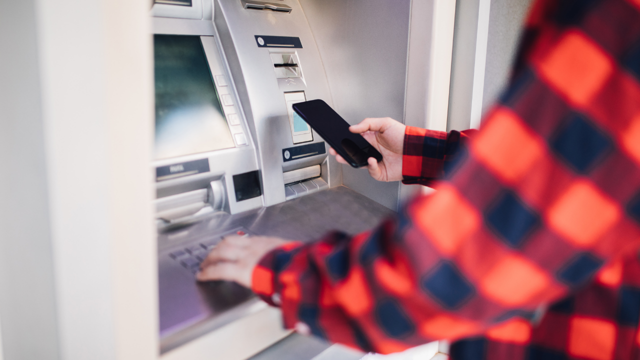 a man in a red plaid flannel shirt using an ATM and holding a phone