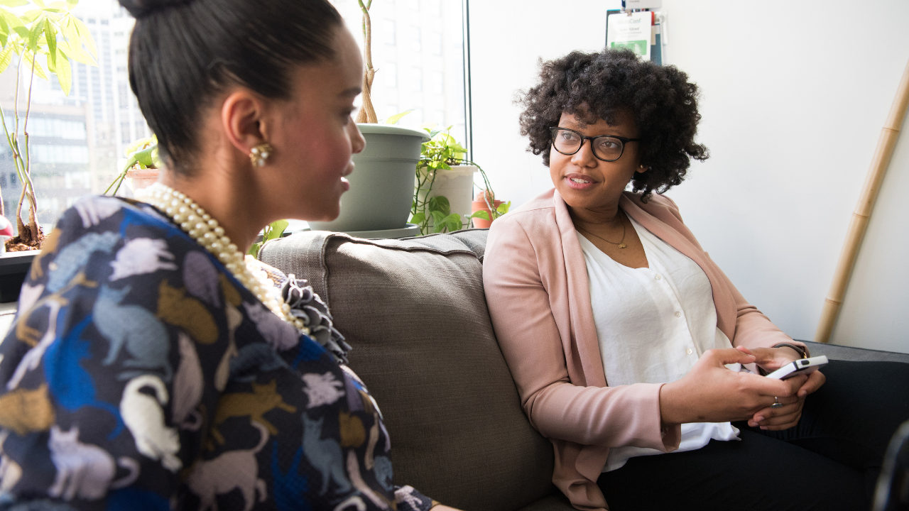 two african american women sitting indoors engaged in a conversation