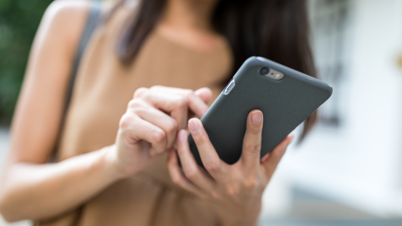 ` a young woman with a beige top holding a grey phone