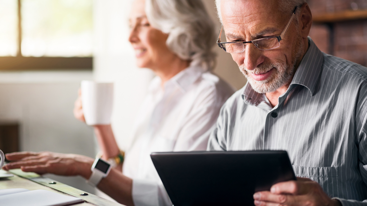 an older man with glasses holding a tablet with his wife at the background drinking a coffee