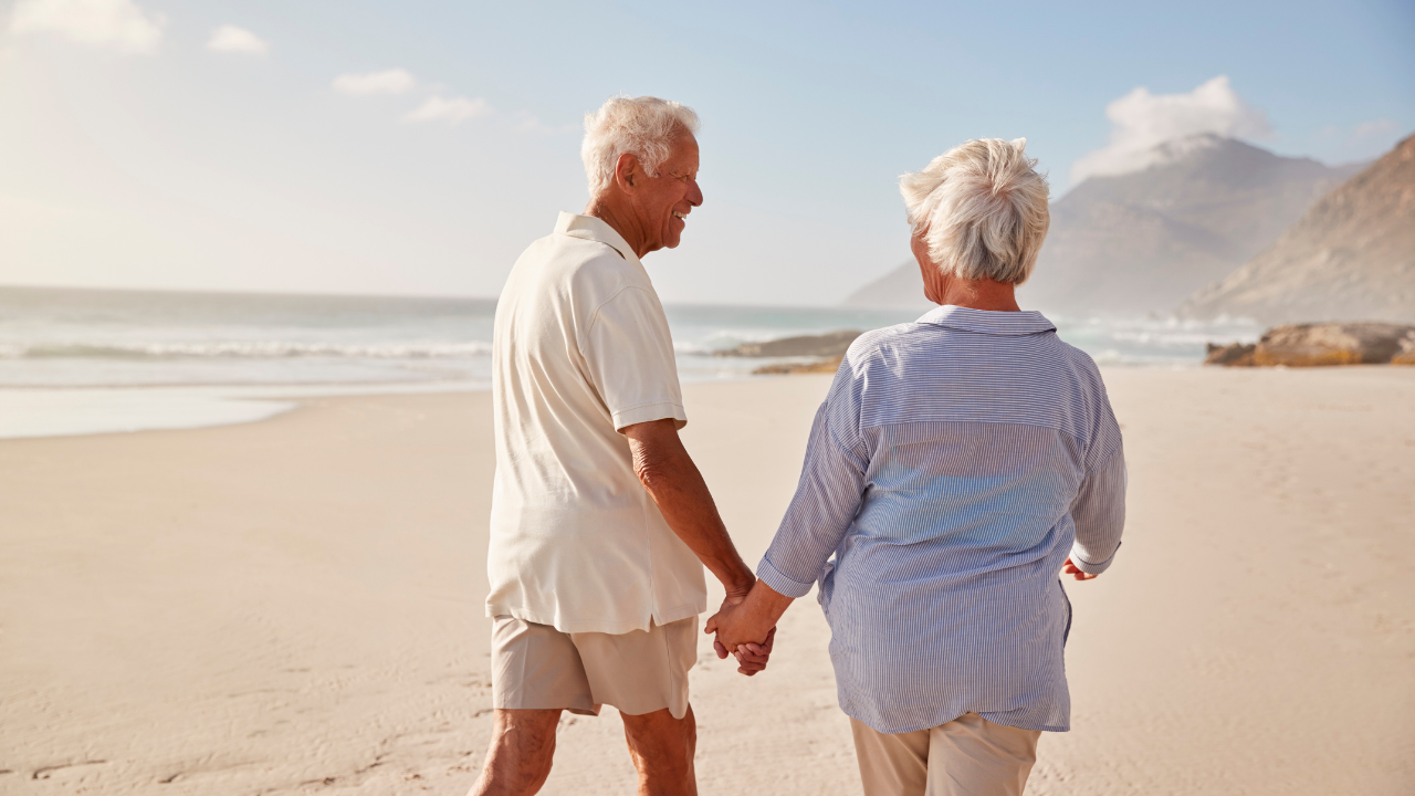 an older couple holding hands on a beach