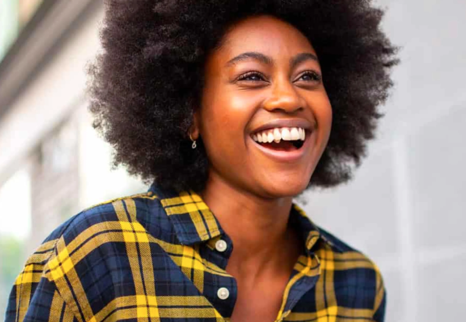 a woman with plaid flannel shirt and afro smiling