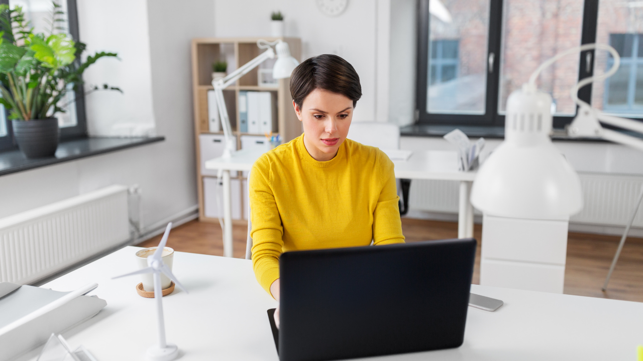 a woman with short brown haircut wearing a yellow shirt working on a black laptop in a bright office