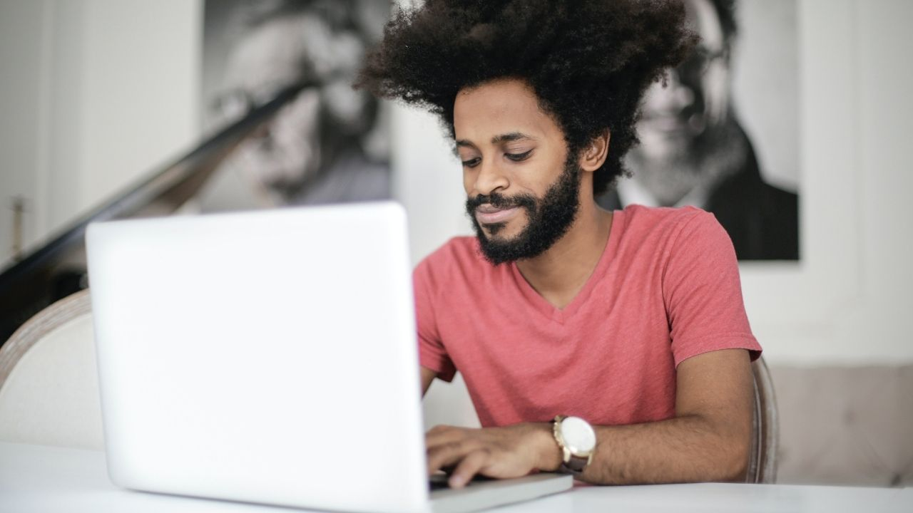 a man with afro wearing a pink tshirt and gold watch looking into a laptop screen