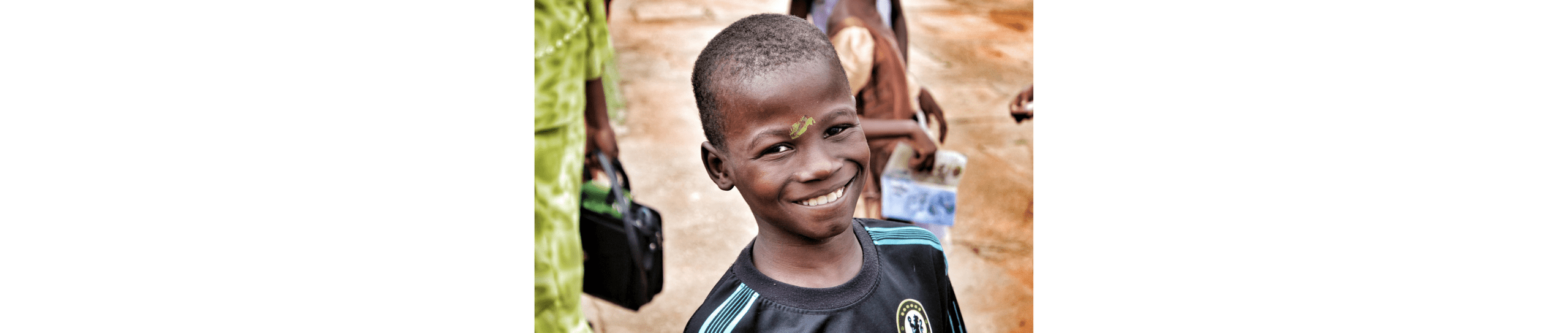 A photo of a young Nigerian boy smiling into the camera