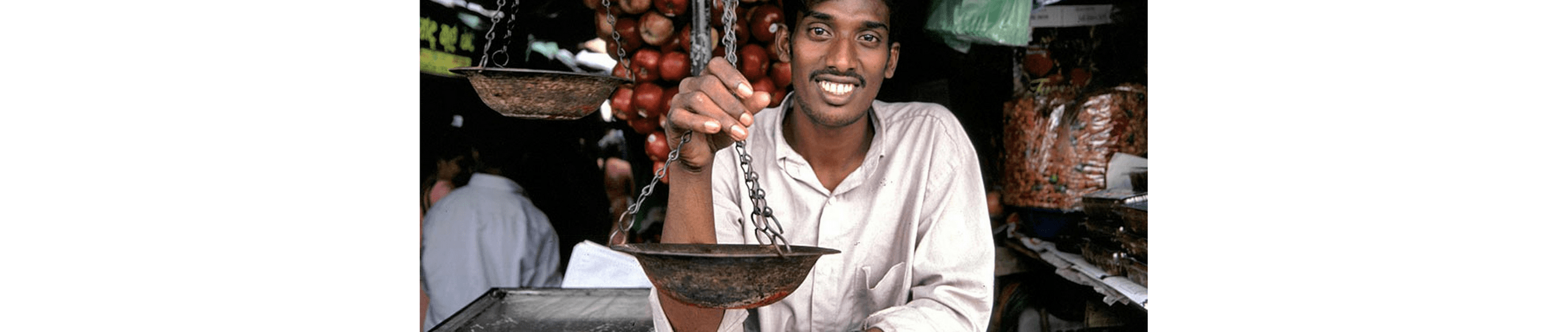 A photo of a smiling shopkeeper in Sri Lanka holding a scale