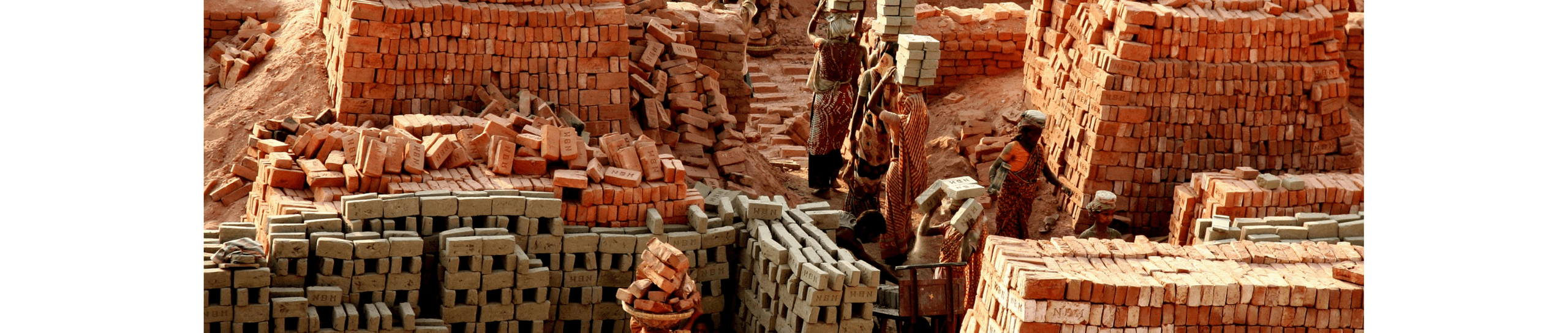 A photo of working women carrying bricks on their head in Bangladesh