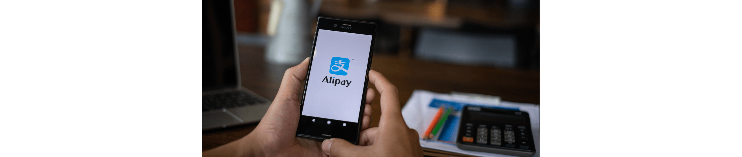 An image of the Alipay logo on a mobile phone