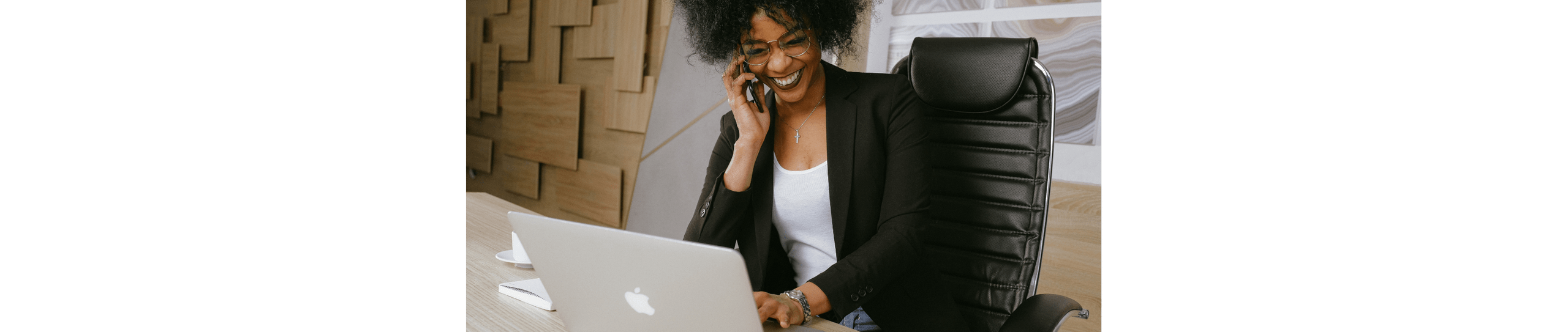 A photo of a black woman holding a phone to her ear and looking into a laptop