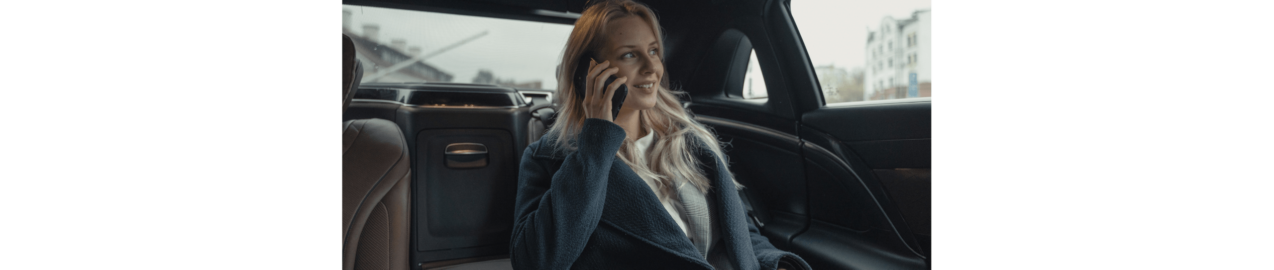 A blonde woman in a car holding a phone up to her ear