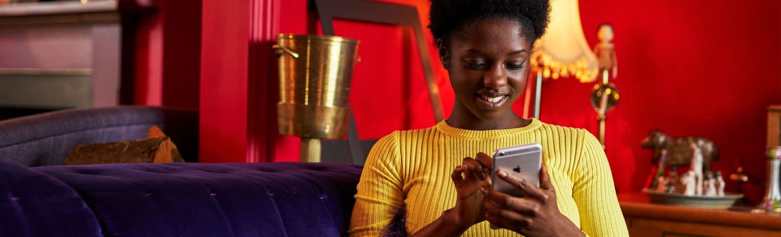 Young African woman on purple sofa and with red background texting on phone.