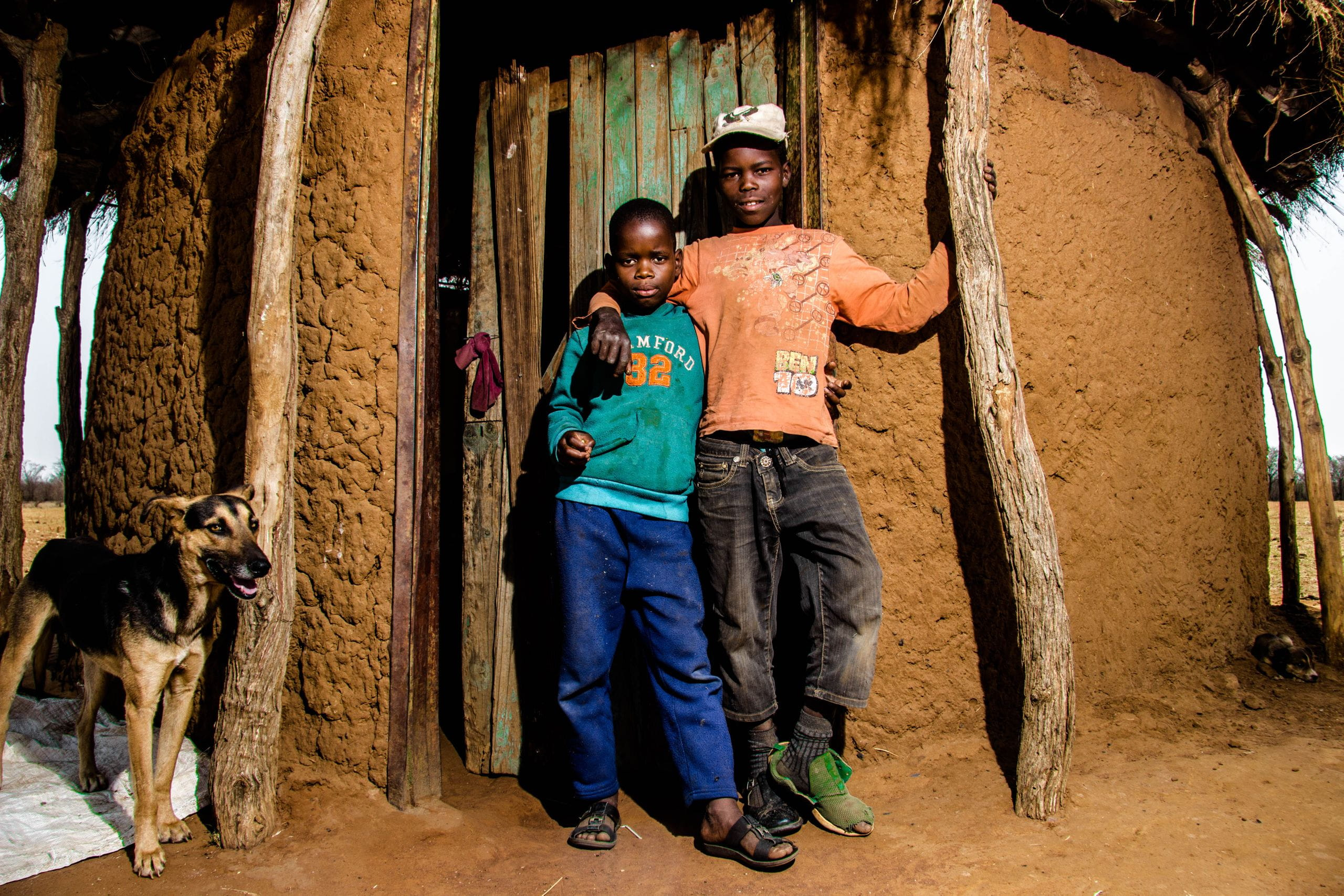 Image of children posing in front a hut in Botswana