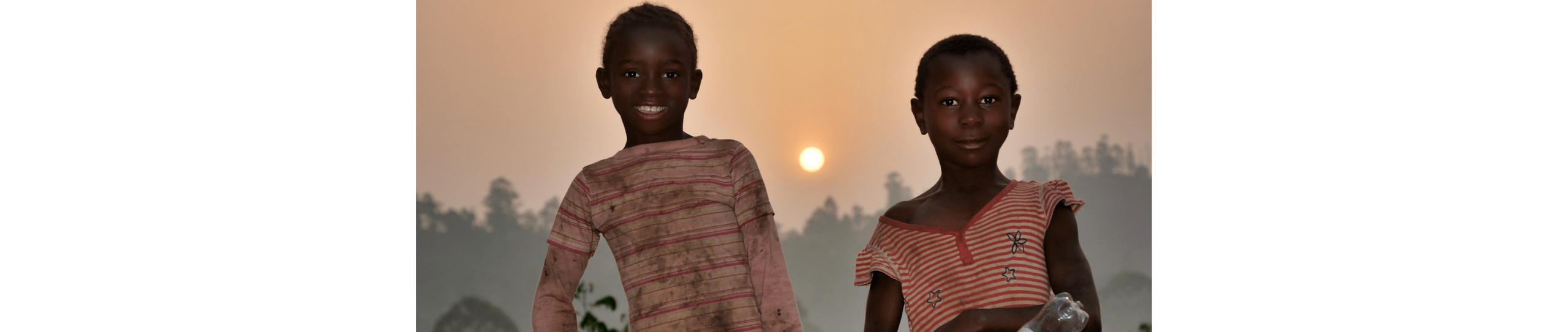Image of two children in front of a sun on an African landscape