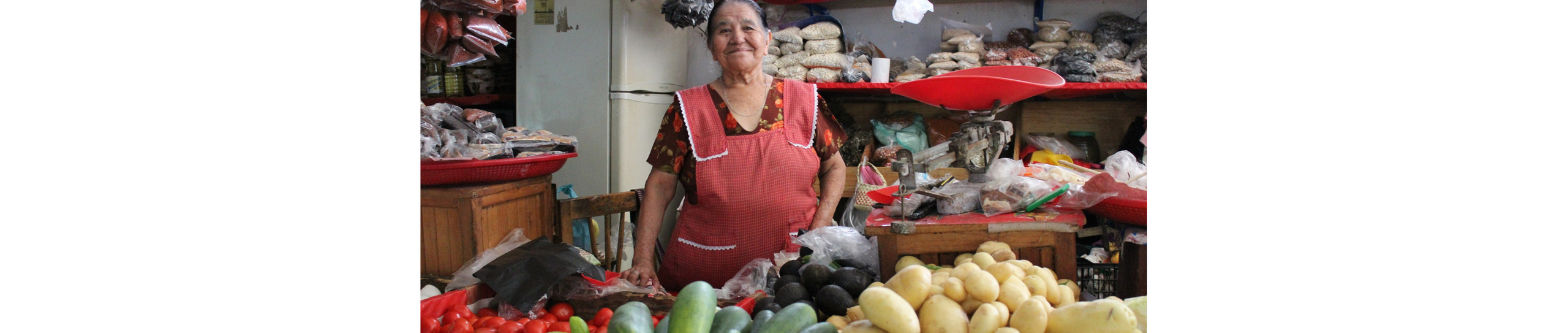 A photo of a smiling Mexican woman inside a traditional shop